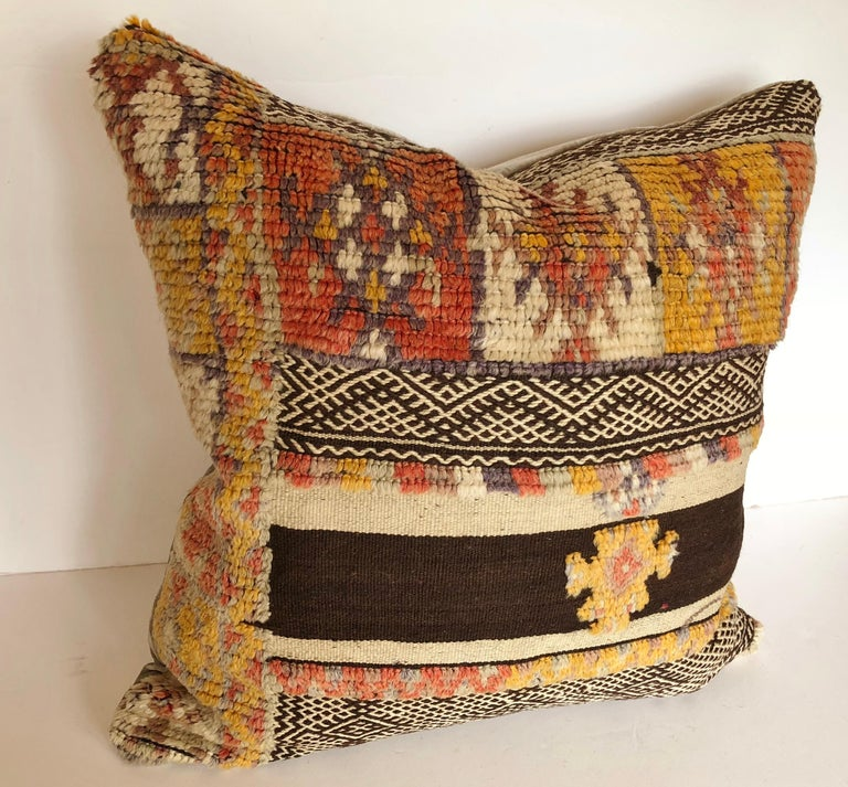 Custom pillow cut from a rare vintage hand loomed wool Moroccan Glaoui rug made by the Berber tribes of the Atlas Mountains. Wool is soft and lustrous with natural dyes. Flat-weave rug is embellished with tufted tribal designs. Pillow is backed in a