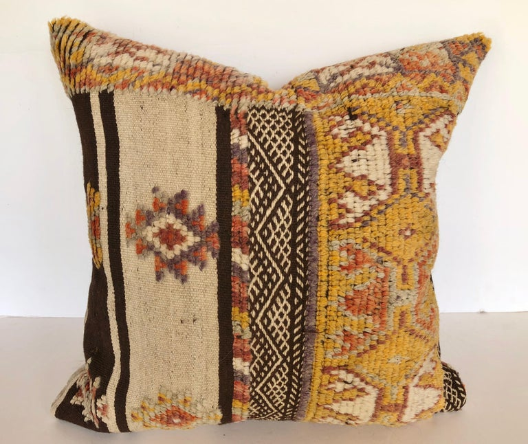Custom pillow cut from a rare vintage hand loomed wool Moroccan Glaoui rug made by the Berber tribes of the Atlas Mountains. Wool is soft and lustrous with natural dyes. Flat-weave rug is woven with tufted tribal designs. Pillow is backed in a