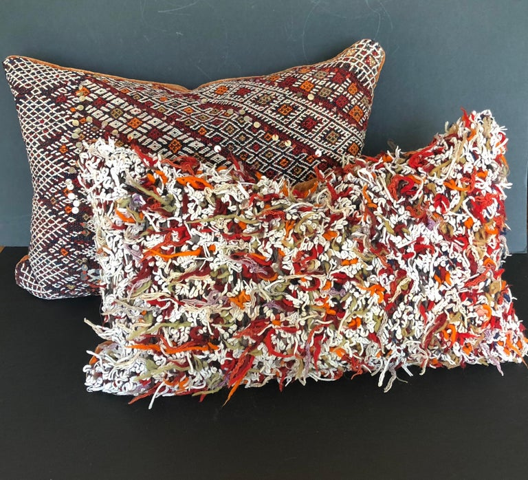 Custom pillow cut from a vintage hand loomed wool Moroccan Berber rug from the Atlas Mountains. The pillow is cut from the reverse side of the rug where all of the wool was left uncut after the weaving process. Pillow is backed in deep paprika