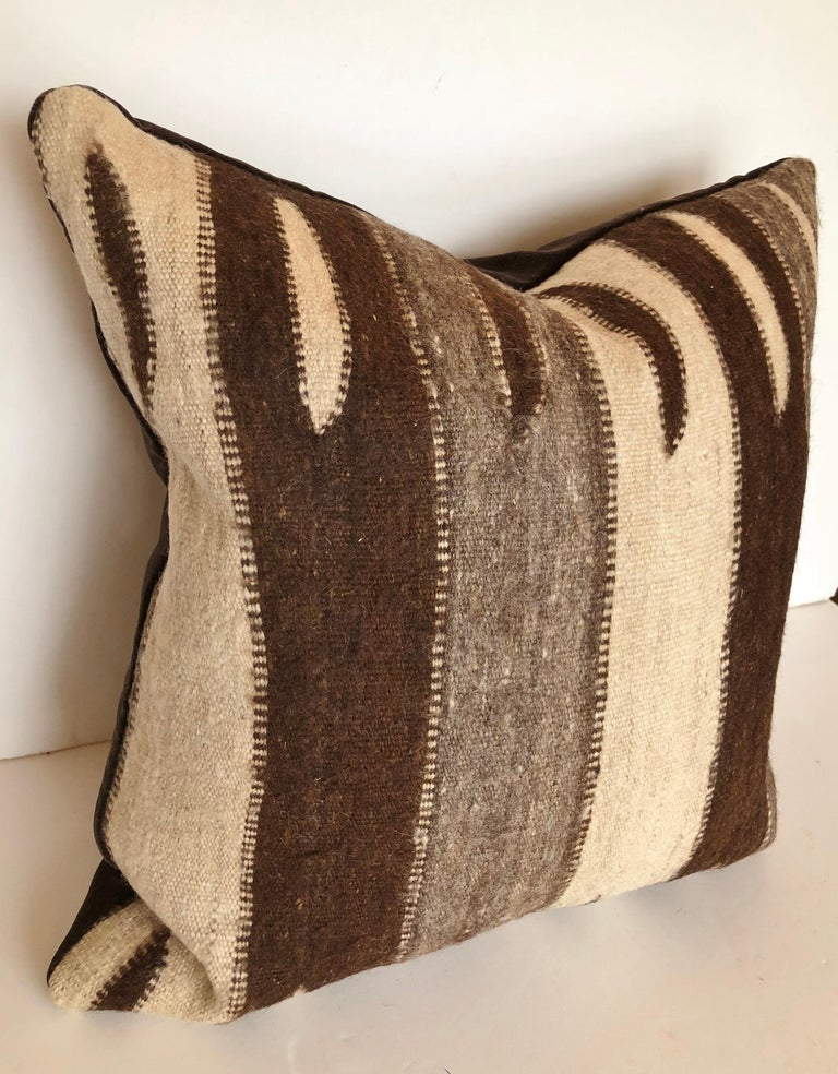 Custom pillow cut from a vintage hand loomed wool Moroccan rug made in the Ourika valley of the Upper Atlas Mountains. A very rare textile, the wool is soft and lustrous with all natural color. The pillow is backed in dark brown velvet, filled with
