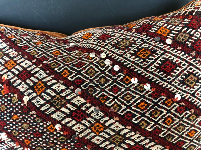 Custom pillow cut from a vintage hand loomed wool Moroccan rug from the Atlas Mountains. Tribal designs are embellished with sequins. Pillow is backed in a deep cinnamon mohair, filled with an insert of 50/50 down and feathers and hand sewn closed.