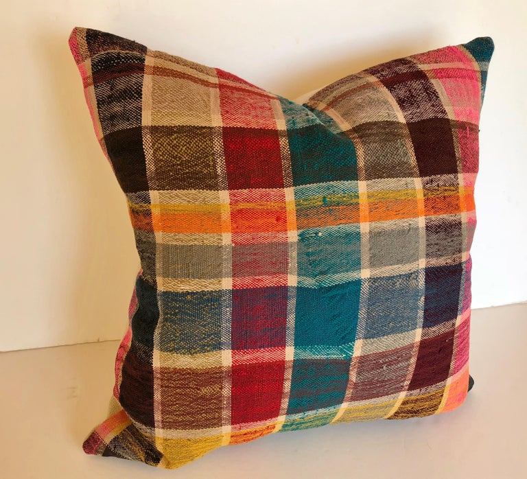 Custom pillow cut from a vintage Moroccan hand loomed cotton Haik or shawl worn by the Berber women of the Mid Atlas Mountains. Woven late 20th century, traditionally plaid with bright colors. The pillow is backed in a linen blend, filled with an