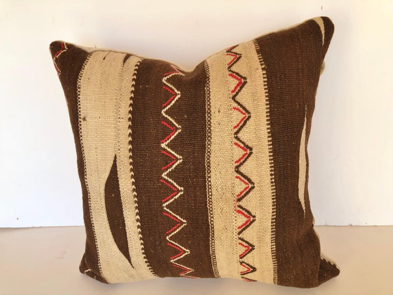 Custom pillow cut from a vintage Moroccan hand loomed wool Ourika rug from the Berber tribes in the Upper Atlas Mountains. The wool is soft and lustrous with tribal designs. Pillow is backed in cream velvet, filled with an insert of 50/50 down and