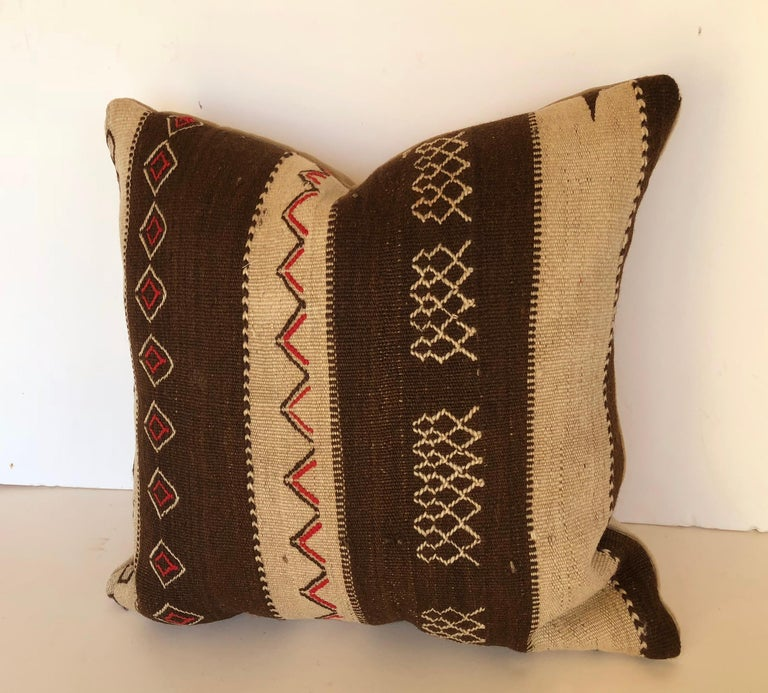 Custom pillow cut from a vintage Moroccan hand loomed wool Ourika rug made by the Berber tribes of the Upper Atlas Mountains. Wool is soft and lustrous with tribal embroidered designs. Pillow is backed in cream velvet, filled with an insert of 50/50