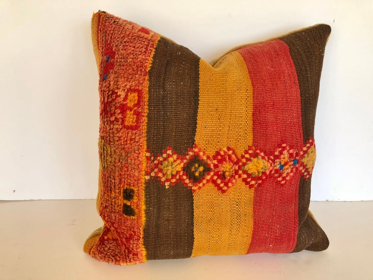 Custom pillow cut from a vintage hand loomed wool Moroccan Berber fug from the Atlas Mountains. Colorful stripes are embellished with tufted tribal designs. Pillow is backed in mohair, filled with an insert of 50/50 down and feathers and hand sewn