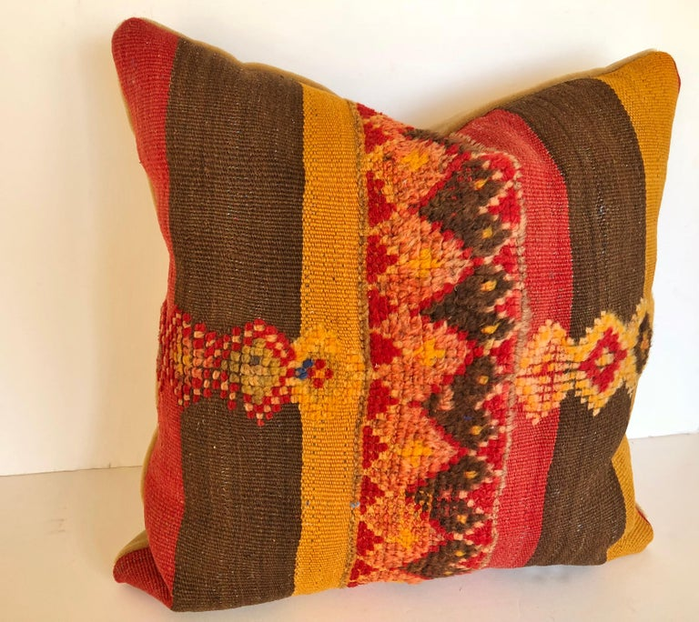 Custom pillow cut from a vintage hand loomed wool Moroccan Berber rug from the Atlas Mountains. Colorful stripes are embellished with tufted tribal designs. Pillow is backed in mohair, filled with an insert of 50/50 down and feathers and hand sewn