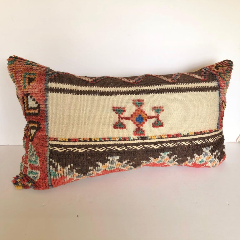 Custom pillow cut from a vintage hand loomed wool Moroccan Glaoui rug from the Atlas Mountains. Wool is soft and lustrous with tufted wool tribal designs over flat-weave stripes. Pillow is backed in velvet, filled with a 100% down insert and hand