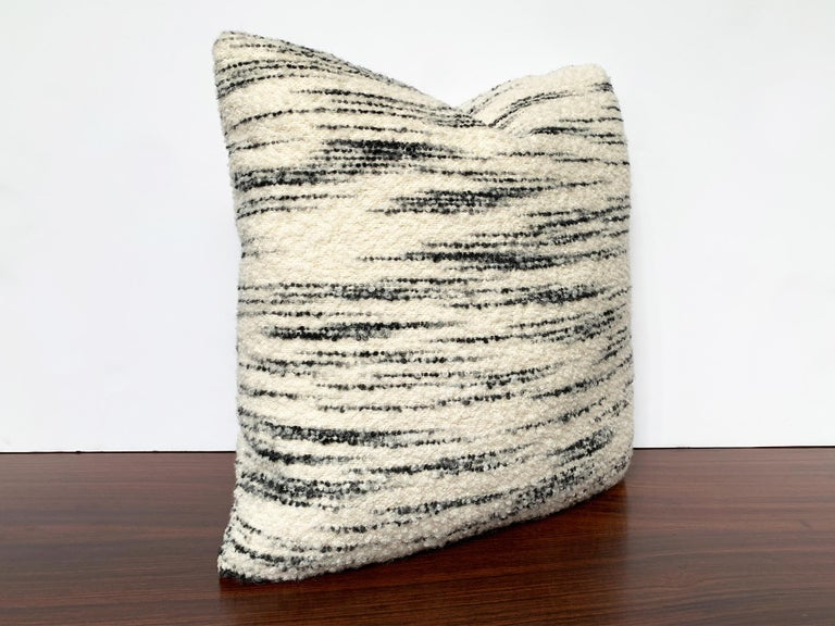 This new, custom made pillow is crafted from a soft wool bouclé made by Schumacher. The fabric is cream-white with horizontal black stripes and has a curly texture. The filling is a combination of foam and down. This is a very cozy pillow for your