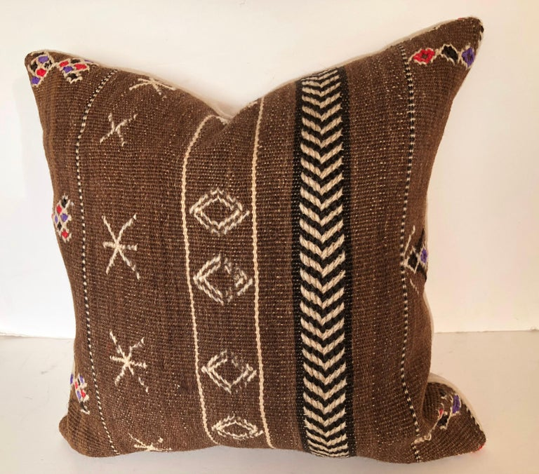 Custom pillows cut from a vintage hand loomed wool Moroccan Berber rug from the Ourika Valley in the Upper Atlas Mountains. Dark brown naturally colored wool has decorative tribal designs. Pillows are backed in cream mohair, filled with an insert of