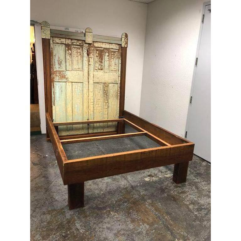A custom bed frame. This custom Queen size bed was constructed from all reclaimed wood and doors as well as decorative Architectural elements. The bed has quite a presence! It does come in pieces, however the headboard stays intact as one piece. If