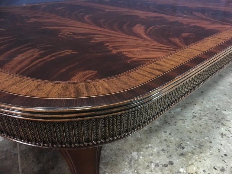 This is a made-to-order large traditional Regency style mahogany dining table made in the Leighton Hall shop. It features a field of slip-matched swirly crotch mahogany from West Africa and satinwood and Santos rosewood borders from South America.