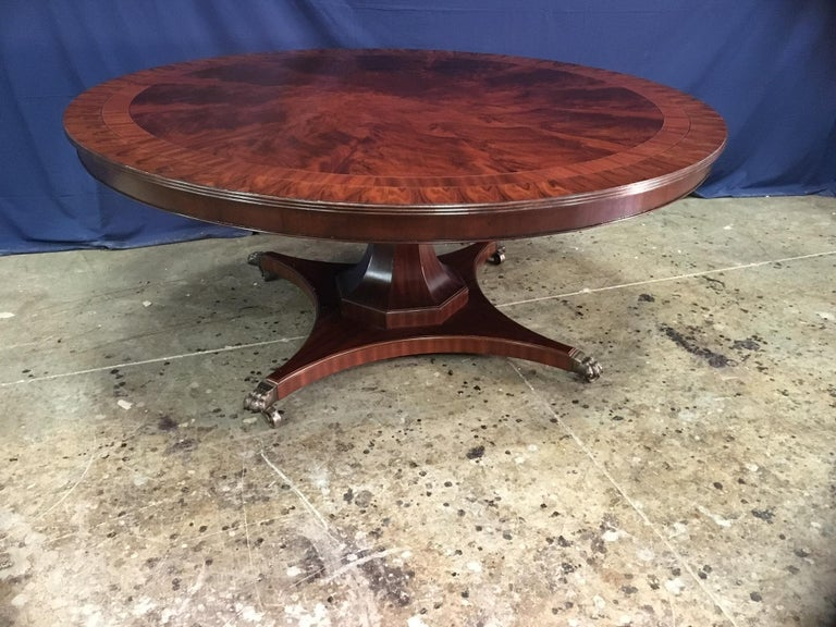 This is made-to-order large round traditional mahogany dining table made in the Leighton Hall shop. It features a radial cut field of west African swirly crotch mahogany and two borders of straight grain mahogany and santos rosewood. It has a hand