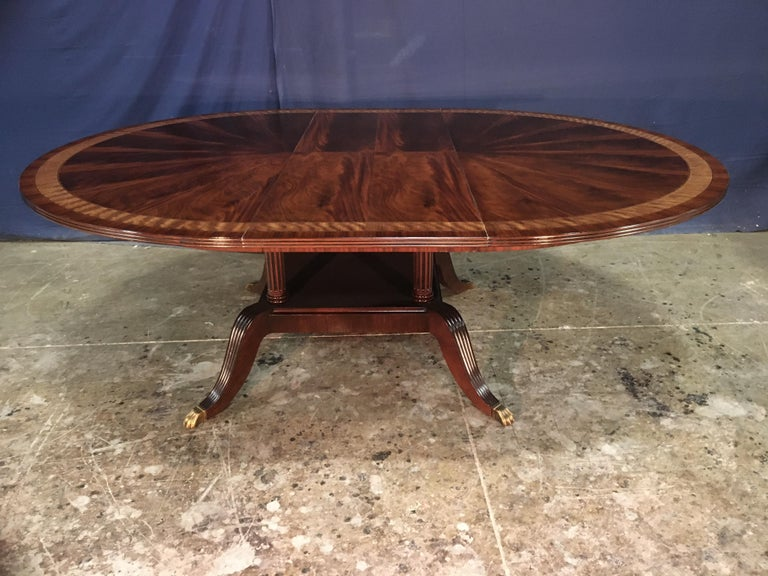 This is made-to-order round traditional mahogany dining table made in the Leighton Hall shop. It features a radial cut field of West African swirly crotch mahogany and two borders of satinwood and Santos rosewood. The top has a medium brown mahogany