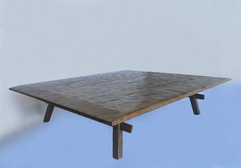Thin profile coffee table based on a rustic antique table from Guatemala. The top is hand finished with a traditionally hand hewn top and distressed to add character. This table can be made in any size and with a variety of finishes. Made in Los