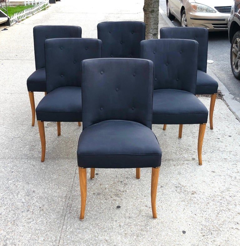 Set of six dining chairs with black silk-upholstered barrel-backed seats with brass rivets on elegantly sabred bleached walnut legs, circa 1930s. From the estate of Alan Moss.