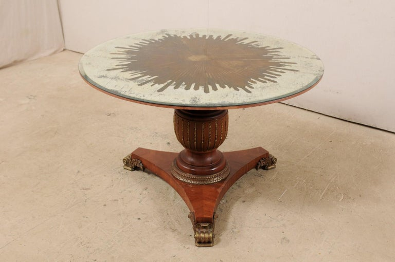 This fabulous custom center table has been fashioned with an artisan-made, round-shaped mirror top, with verre églomisé sunburst center, top which rests upon a vintage carved-wood pedestal base. The gold verre églomisé star or sunburst fills up the