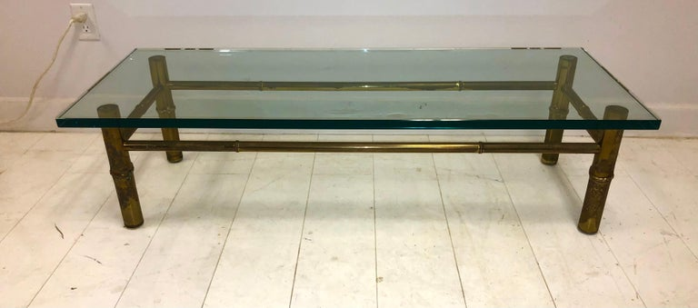 """Unique, one of a kind, solid cast brass table with 1"""" thick green glass top, circa 1953. The second largest of three faux bois bamboo-form low tables we have available, all from the grand living room of the Kandell Penthouse apartment at the"""