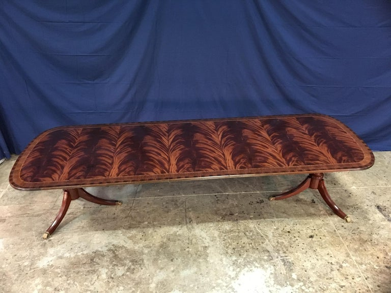 This is a made-to-order large traditional mahogany dining table made by Leighton Hall. It features a field of slip-matched swirly crotch mahogany from West Africa and straight grain mahogany and Santos rosewood borders from South America. The