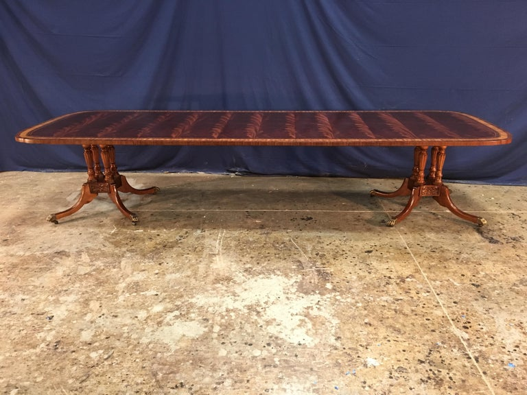 This is a made-to-order traditional mahogany dining table made by Leighton Hall. It's double scalloped corners gives it a unique delicate shape. It features a field of slip-matched swirly crotch mahogany from West Africa and satinwood, burled walnut