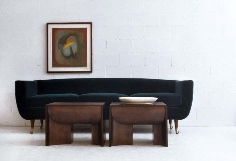 This upholstered sofa is highly stylized and very comfortable from Chicago-based American-designer William Collins collection, it has finely finished wood legs and curled bronze-finished sabots front and back. The legs come in three wood finishes