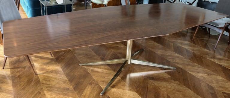 Custom pedestal dining table with walnut veneer and brass leg.   Measures: End depth: 34