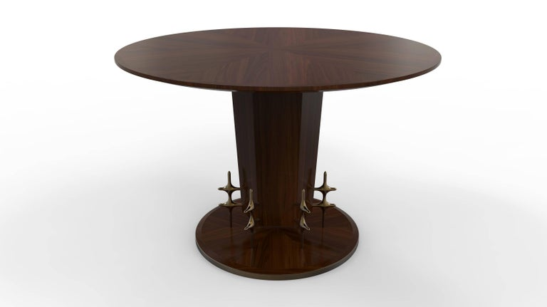 The William Collins collection centre table in solid wood and veneers featuring a pie-cut top and base, raised pedestal on solid bronze legs, and bronzed steel base trim. Available as custom single or double pedestal dining table. 