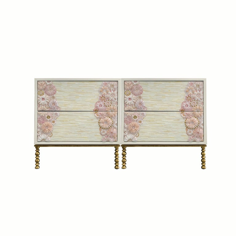 The blossom nightstand by Ercole Home has a 2-drawer front, with a white lacquer wood finish. Handcut glass mosaic in variety shades of gold, pink, white and ivory decorate the surface in Blossom and stripe mosaic pattern. The decorative metal