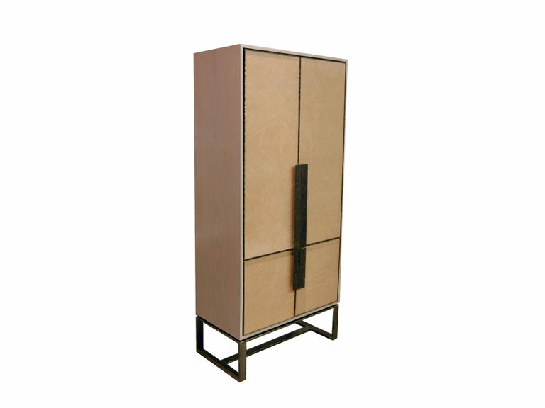 The Chelsea bar cabinet by Ercole Home has a 4-door front, with sand wood finish on oak. Hand-stretched leather in sand brown decorates the door fronts. Hand-hammered metal framed doors, handles, and base in dark bronze metal finish. The cabinet