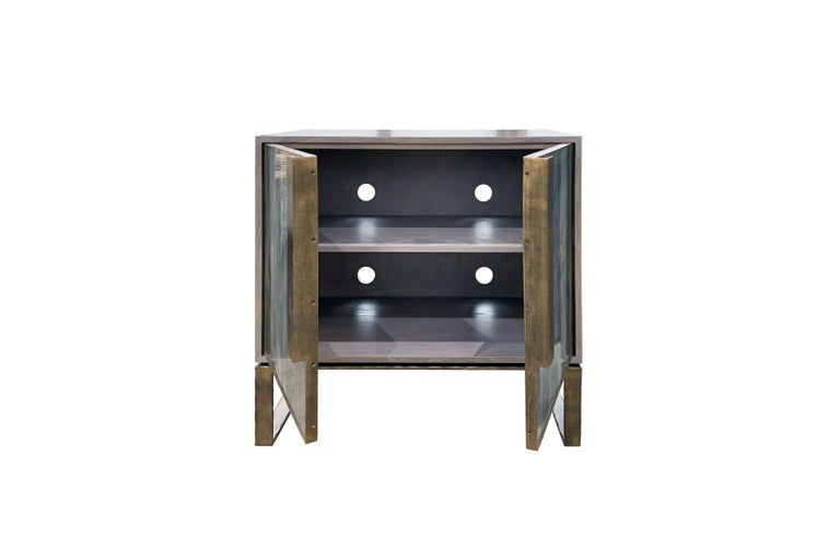 The Chelsea credenza or sideboard by Ercole home has a 2-door front, with Earl Gray Ceruse wood finish on oak. Handcut glass panels in Wispy Gray Silver are on the door surface. Hand-hammered metal framed doors, handles, and base in dark bronze