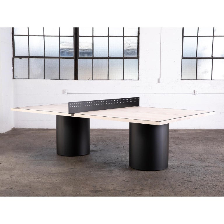 The Column Ping Pong Table is our modern take on a classic game. The table's matte wood top is supported on two metal columns that can be powder coated in matte black, white or painted to your specifications. The tabletop is divided by a