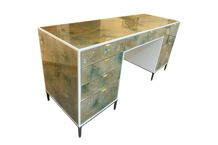 The Mystic Byzantine Gold Green vanity by Ercole Home has a 9-drawer, with ivory wood finish on oak. Hand painted eglomise glass panels are inset on the surface. There are nine pulls in brushed brass finish. The hand hammered metal base is in