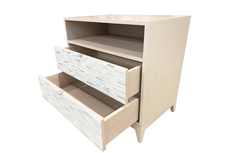 The Milano nightstand by Ercole Home has a 2-drawer front and open shelf, with washed ivory wood finish on oak. Handcut glass mosaics in icy white, wispy white, and silver decorate the surface in a horizontal regular stripe pattern. There are two