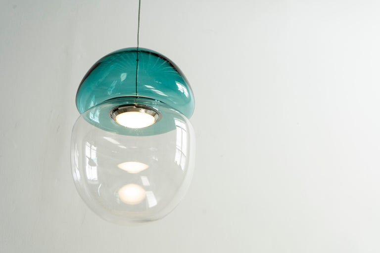 Dew and drop is a pendant lamp made of two pieces of hand blown glass, resembling a dewdrop resting on top of a falling droplet of water. The light is trapped in between the glass, creating natural shades and reflections all around.  The dew and