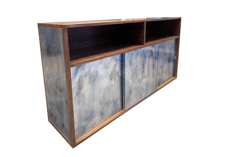 The Mystic buffet or credenza by Ercole Home has a 3-sliding door front, with natural wood finish on walnut. Hand painted glass panels in Midnight Moon are on the door and side surface. The platform base with 2'' toe kick in the same finish as the