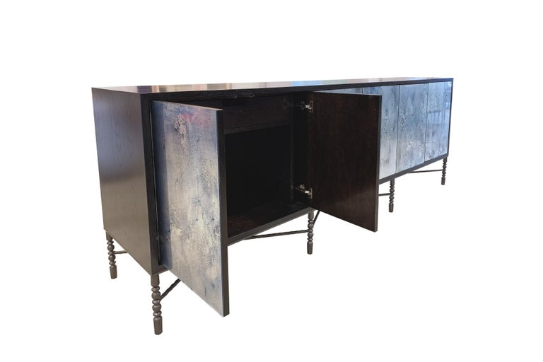 The Mystic buffet or credenza by Ercole home has a 6-door front, with Espresso wood finish on oak. Hand-painted glass panels in Midnight Moon are on the door surface. The decorative vintage style base with hand-hammered X-shape stretchers in