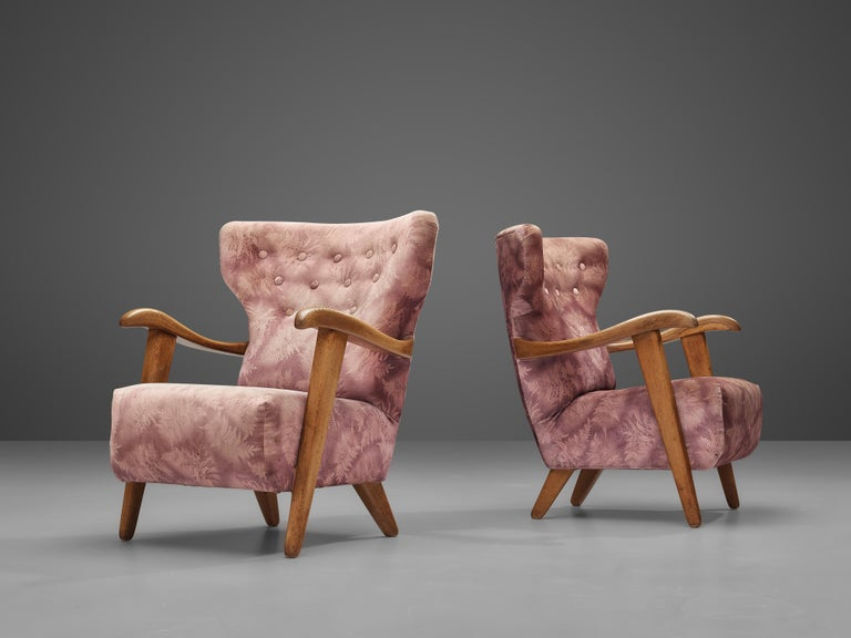 Lounge chairs, oak, fabric, France, 1960s  This wonderful pair of French lounge chairs features a backrest with winglike upper ends. Tufted details structure the high backrest. More dynamic appeal is created by the curved armrests in oak.   Please