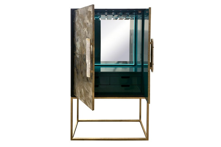 The gold dust bar cabinet by Ercole Home has a 2-door front, with matte black exterior and green lacquer interior wood finish.