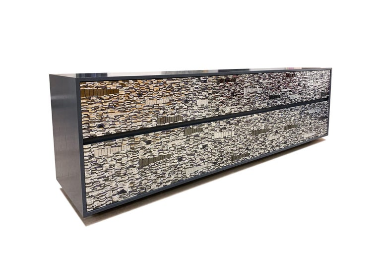The Ravenna chest by Ercole Home has a 6-drawer front, with 2-3/8 H platform wood base. Handcut glass mosaic in grey mirror, silver, mirror, and purple mirror decorate the surface in Ravenna Mosaic pattern. Dark gray Lacquer wood finish on
