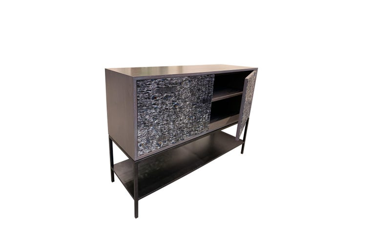 """The Ravenna cabinet by Ercole Home has a 2-door front, with metal base in natural steel finish. The metal shelf is 5"""" H off the floor. Handcut glass mosaic in grey mirror, pewter, antique pewter, silver, antique silver, fume, notte and bronze"""