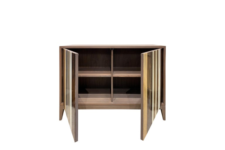 The Milano buffet by Ercole home has a 2-door front, with gray stain on American black walnut finish. Handcut glass stripes in ivory, butterscotch, medium chocolate, and dark chocolate decorate the surface of doors. There is one adjustable