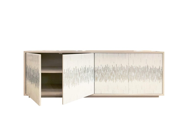 The platform wave buffet by Ercole Home has a 4-door front, with washed ivory wood finish on oak. Handcut glass mosaics in icy white and silver, wispy white silver decorate the surface in a continuous wave pattern. There is one adjustable interior