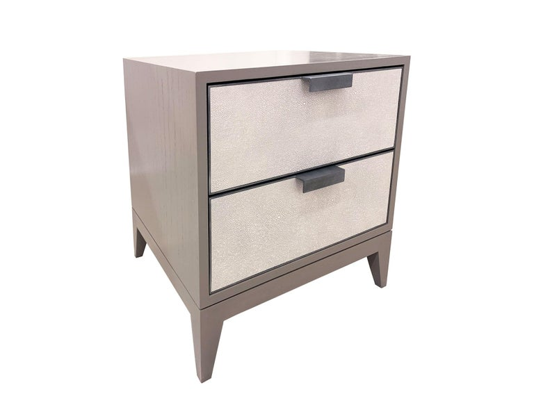 The Milnao Shagreen Leather Nightstand by Ercole home has a 2-door front, with Linen 2 wood finish on oak. White/ light gray shagreen leather with hand-forged metal frames in pewter patina are on the drawer surface. Custom sizes and finishes are