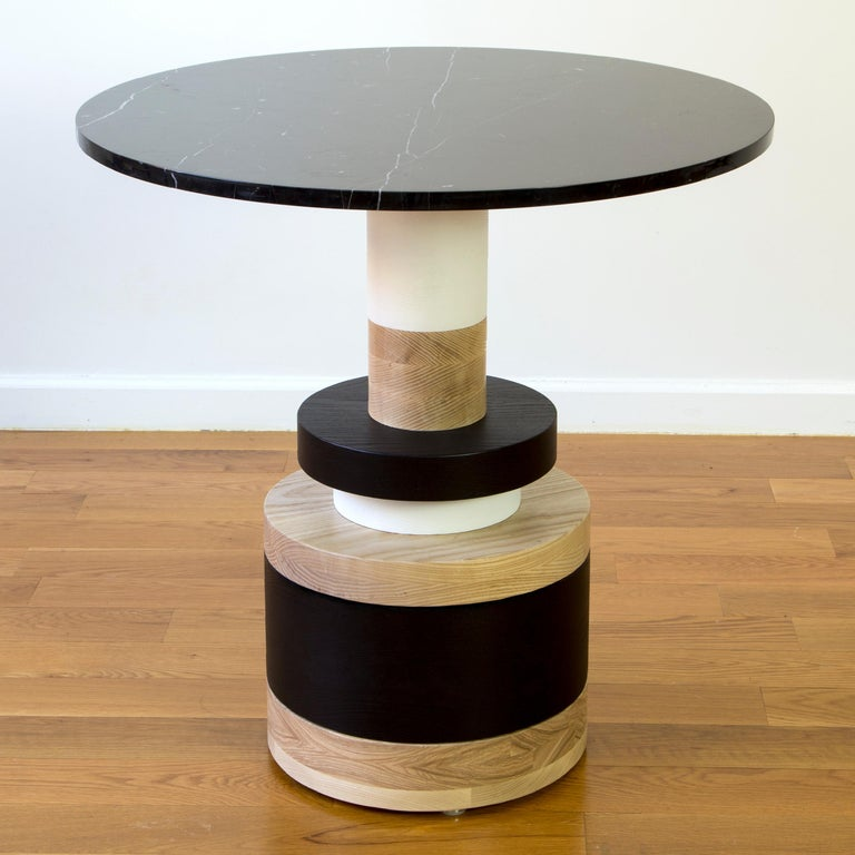 "The Sottsass-inspired ""Sass Dining Table"" is a bold, graphic statement piece. A honed Carrara marble top sits on an Amish-made base composed of painted and stacked wood circles. Made to order.  The version as shown is 30"