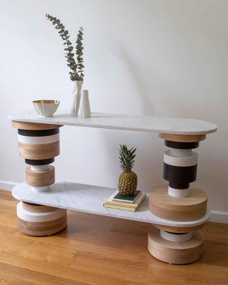 "The Sottsass-inspired ""Sass Console Table"" is a bold, graphic statement piece. A honed Carrara marble top sits on an Amish-made base composed of painted and stacked wood circles. Made to order.