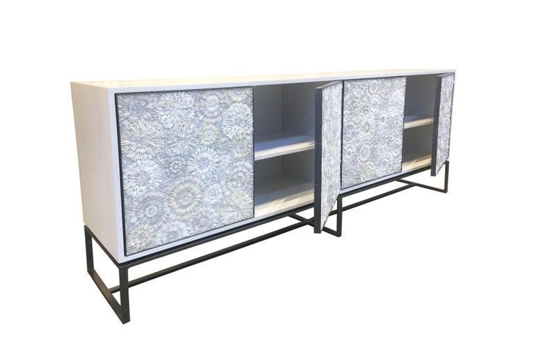 The Blossom serving buffet by Ercole Home has a 4-door front, with hand-hammered metal base and door frames in bronze finish.  Handcut glass mosaic in variety shades of white and ivory decorate the surface in Blossom mosaic pattern. Washed White