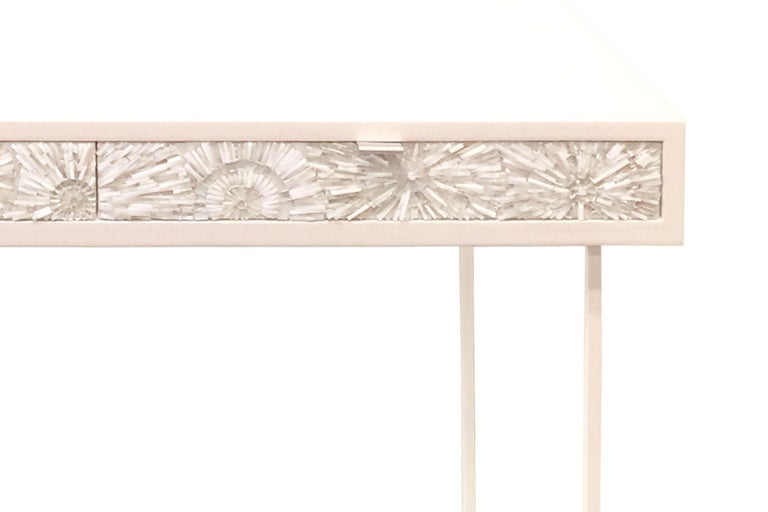 The Pavia Blossom desk/vanity by Ercole Home has a 2-drawer, with a painted white wood finish on oak. Handcut glass mosaics in white and silver decorate the drawer fronts in blossom (3-dimensional flowers) pattern. There are two aluminium pulls in