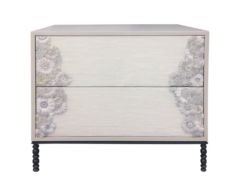 The Blossom nightstand by Ercole Home has a 2-drawer front, with Misty Gray lacquer wood finish. Handcut glass mosaic in variety shades of white and ivory decorate the surface in Blossom and stipe mosaic pattern. The decorative metal base is in Dark