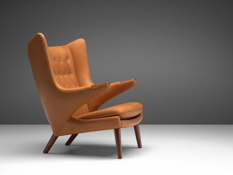 Hans J. Wegner, lounge chair Model AP 19 'Papa Bear', reupholstered in cognac analine leather and ebonized beech legs, Denmark, 1951 design, production 1970s.  This Papa Bear is reupholstered on request in our in-house atelier. This semi-wingback