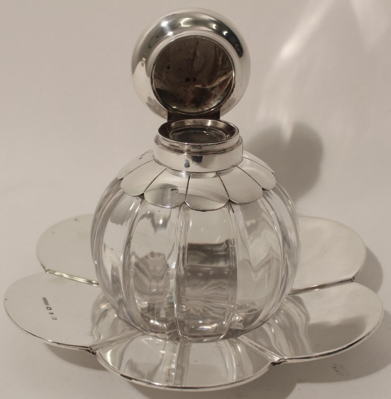 Very unusual cut crystal and silver floral design inkwell with hallmarks for Birmingham, John Grinsell & Sons, 1890. The ribbed body, topped with a silver lid and collar in the form of stylized petals, echoed in the pattern of the silver dish