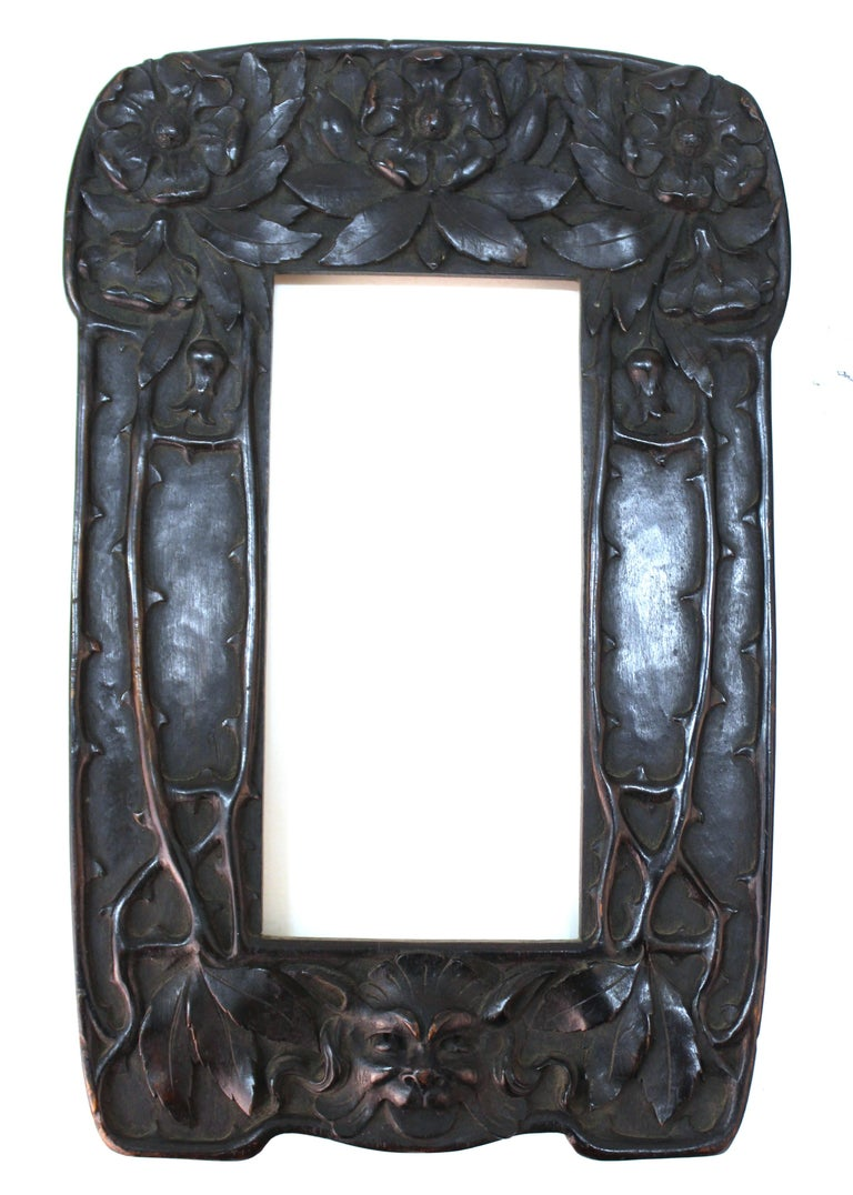 Italian Art Nouveau mirror with an elaborately carved wood frame, created by Cutler & Girard in Italy. The frame has carved roses on the upper part, thorns on the sides and the head of a grotesque on the bottom part. The piece has a makers label on